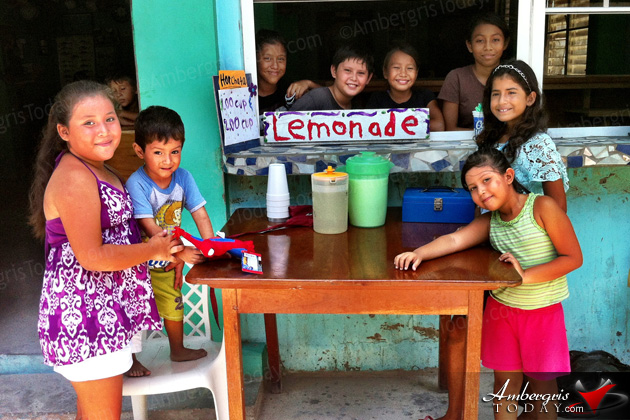 Children set up lemonade stand on hot summer day