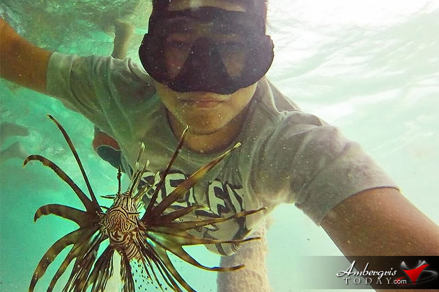 Local tour guide takes selfie with poisonous Lion Fish in San Pedro, Belize