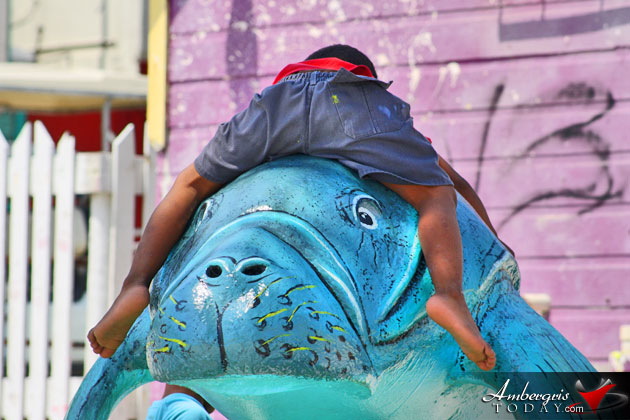 Young boy enjoys manatee sculptur at Central Park, San Pedro, Ambergris Caye