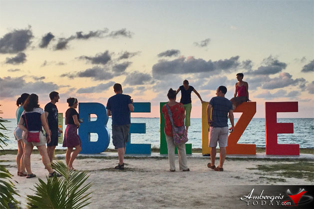 Tourists take pictures at the popular Belize sign in Belize City