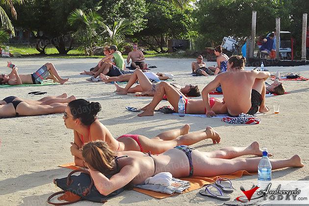 Belize Tourists bask in the sun on beach at the Caye Caulker Split
