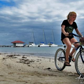 Girl rides bike along Ambergris Caye Beach followed by her pet dog