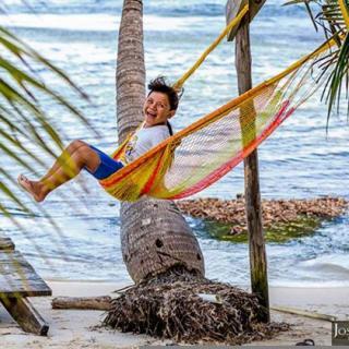 Grild on hammock on the beach, San Pedro, Ambergris Caye, Belize
